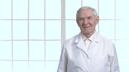 šklebící : Old cheerful grandpa in white suit. Portrait of smiling scientist in bright windows frames background.
