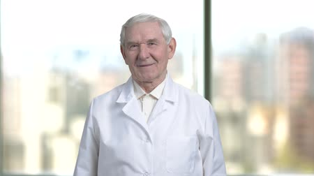 splatnost : Old senior cheerful man in white coat smiling. Blurred city view from windows background. Dostupné videozáznamy