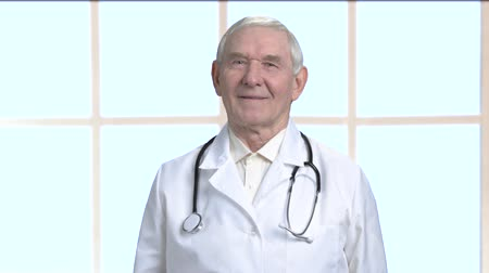 terapeuta : Senior therapist with stethoscope. Friendly old doctor in front of big framed windows background.