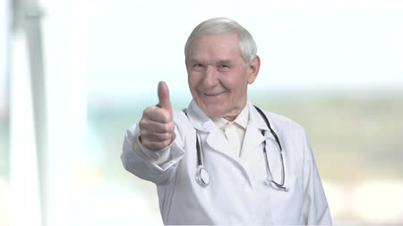splatnost : Old cheerful laughing doctor showing thumb up. Senior medical specialist showing approval gesture in blurred background.