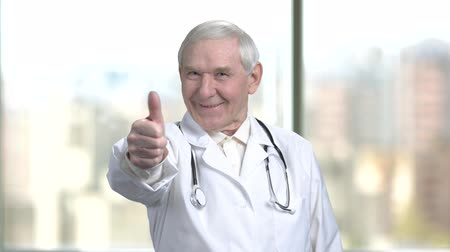 splatnost : Happy old doctor shows thumb up. Senior physician with stethoscope shows you are fine. Blurred city from window background.