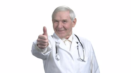 dede : Senior doctor shows thumb up in white isolated background. Old therapist with grey hair showing thumb up and rotating.