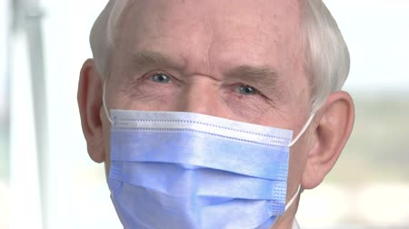close cropped : Close up doctor face with mask. Senior old dantist face with protective mask, blurred background.