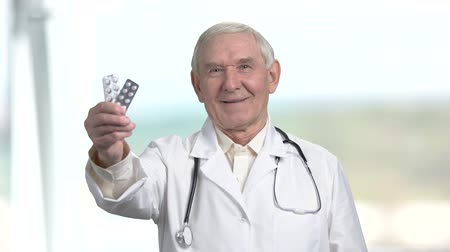 terapeuta : Old senior doctor with two packs of pills and thumb up. Therapist recommend packs of medicine, bright blurred background.