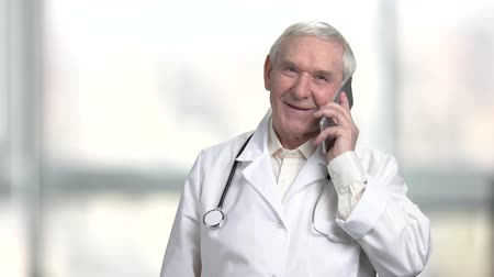 メディケア : Positive cheerful senior doctor talking on the phone. Portrait of old physician with stethoscope talking on smartphone. Bright blurred windows background. 動画素材