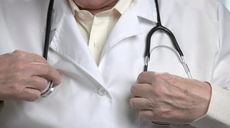 examining : Close up stethoscope on doctor. Old male doctors hands put on stethoscope on his neck. Fix and correct concept. Stock Footage
