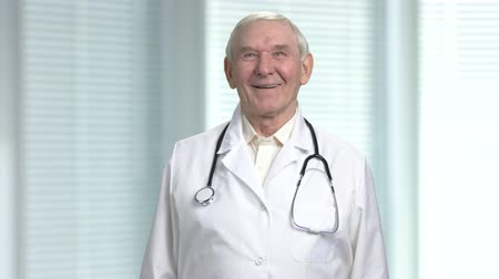 jalousie : Old male doctor laugh at your jokes. Blurred windows with louvers background. Stock Footage