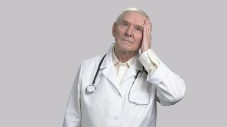 плохо : Portrait of serious gloomy face of an old doctor. Frowning old physician in grey isolated background. Стоковые видеозаписи