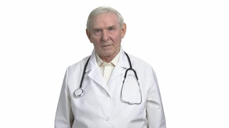 хмурый : Concerned old doctor worry about you. Frowning physician in white isolated background. Стоковые видеозаписи