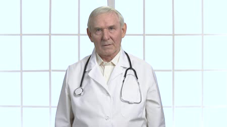 carrancudo : Worried serious old doctor with stethoscope portrait. Bright checkered framed windows background.