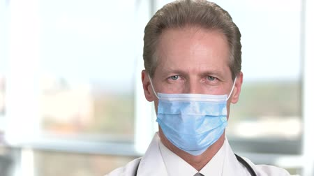 protective suit : Cheerful mature male doctor in protective mask. Physician smiling in medical protective mask on abstract blurred background in bright room in hospital.
