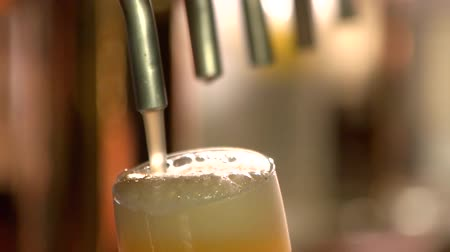 overfill : Close up light beer overfilling glass, slow-mo. Pouring a pint of draft beer from the crane.