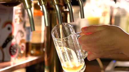 кувшин : Bartender pouring fresh light ale, slow-mo. Man hand drawing beer from tap in an glass. Стоковые видеозаписи