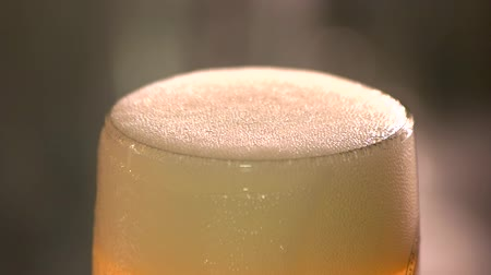 overfill : Cutting beer froth, slow-mo. Close up beer head froth carefully cutting with knife.