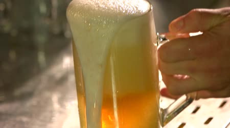 overfill : Close up put overflowing beer on the table, slow-mo. Half mug beer with froth overflowing.