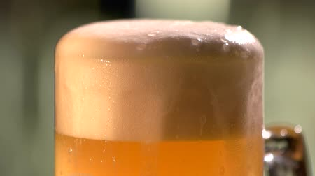 overfill : Delicious mug of lager beer. Head of pint of lager beer slowly moving around.
