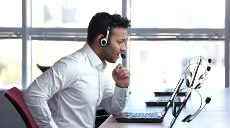 dispatcher : Businessman is trading online. Man is discussing about bussiness using headset and web camera, huge bright windows background. Stock Footage