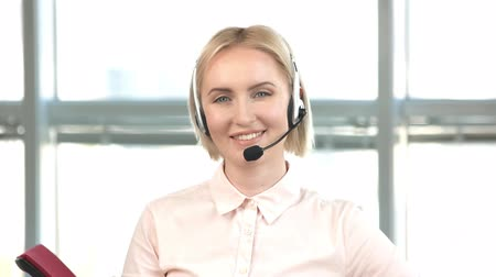 dispatcher : Blond woman with headset showing thumb up. Female office worker face with headset happily smiling.