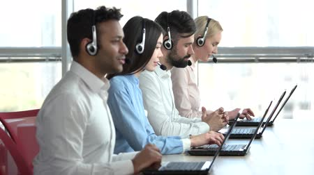 dispatcher : Line of call centre employees working on a laptop computers. Business people group with headphones giving support to customers in bright office.