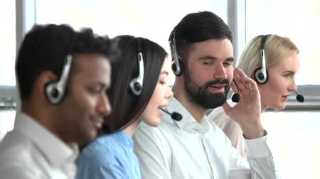 dispatcher : White young bearded man call center operator smiling. Tech support operator turning his head. Agree and nodding head. Stock Footage
