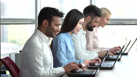 computer programmer : Smiling people working together in office. Team of programmers working in a team, huge windows background. Stock Footage
