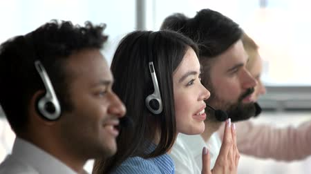 operators : Asian girl working as dispatcher in office. Japaneese female dispatcher with colleagues, close up, side view.
