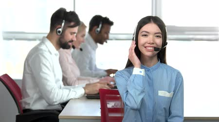 подтверждать : Cheerful asian girl in call center with headset agreeing. Adorable japaneese girl in office, colleagues background. Стоковые видеозаписи