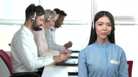 подтверждать : Asian girl talking with headset. Typing people in office background. Office woman in striped shirt. Стоковые видеозаписи