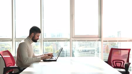 előcsarnok : Young bearded man working as freelancer on laptop. Man working on laptop in office with windows background.
