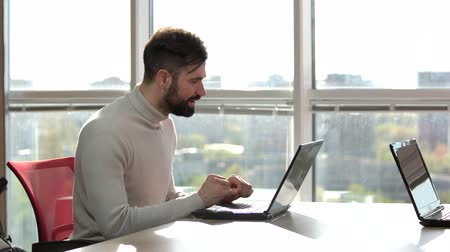 keyifli : Handosome bearded man pondering while working on laptop. Thougtful caucasian bearded man with laptop. Bright windows background.