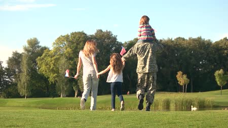 homeland : Family coming to park lake. Soldier in militarty suit walking with family, back view.