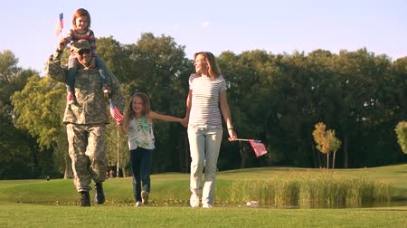 idílio : Patriotic family with military father. Walking soldier with wife and daughters with USA backgrounds. Vídeos