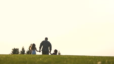 go away : Back view of going military man with two children. Walk away in the horizon. Stock Footage