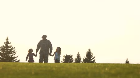 there : Low ground view, soldier with kids walking. Militarty father with two daughters move straing forward.
