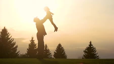 homeland : Father playing with daughter in Park, slow motion. Side view, daddy and daughter in the park in the evening. Stock Footage