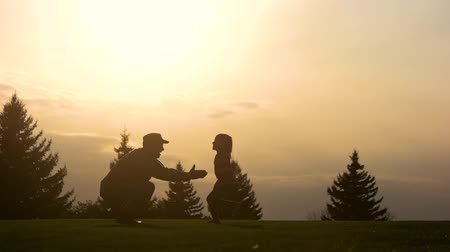 homeland : Father lifting child in air over scenic sunset sky. Daddy and daughter playing together, side view, slow motion.