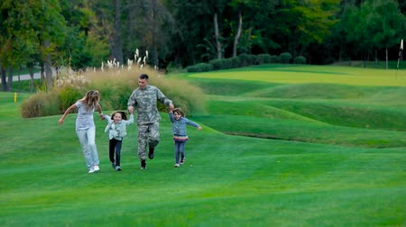 vzdálený : Front view military father with his happy familiy walking and jumping. American usa soldier at the facation with family, front view, slow motion.