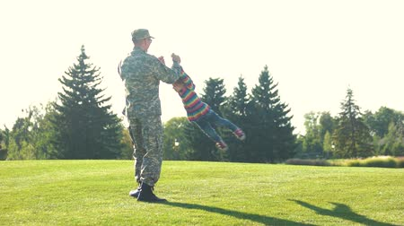 obránce : Father and daughter playing circling around at the park. Daddy soldier playing with little daughter in the sunny lawn at the day. Dostupné videozáznamy