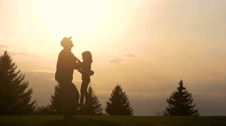 homeland : Father having fun with daughter silhouette. Father lifting up his daughter in the park while sunset. Stock Footage