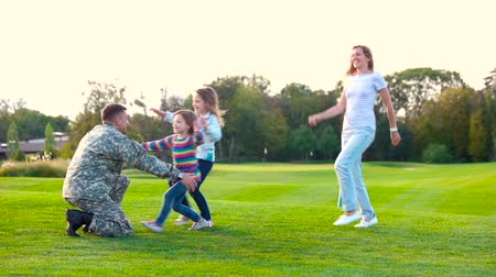 heroes : Daughters and wife running into daddys arms. Children greeting military father.