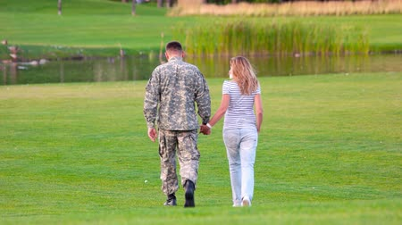 homeland : Back view military man on date in a park lawn. Happy soldier with woman on glade, rear view.