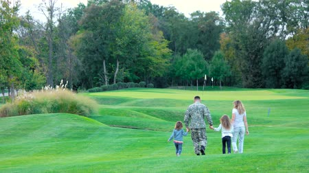 go away : Military man and wife walking and playing with daughters,rear view. Little girls jumping on lawn, back view.