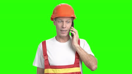 вырезка : Construction worker talking on cell phone. Mature foreman talking on mobile phone on chroma key background. Confident foreman with mobile phone.