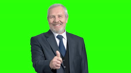 substituição : Elderly businessman giving thumb up. Old man in formal wear showing thumb up gesture on chroma key background. Symbol of agreement and success.