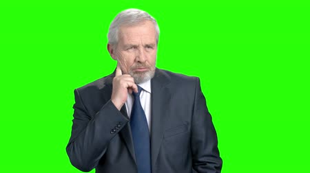 analyzes : Elderly thoughtful businessman, green screen. Confident senior man in formal wear with pensive expression, chroma key background. Thinking about new opportunities.