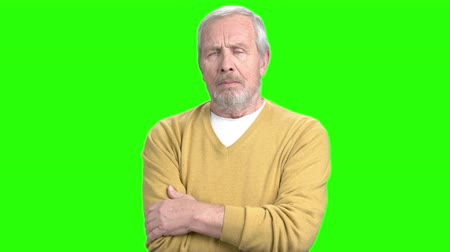 migrén : Elderly man having migraine, green screen. Senior man in pullover suffering from headache, chroma key background. Hypertension and headache concept.