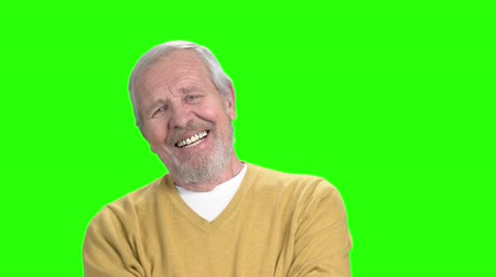 tenderloin : Smiling elderly man, green screen. Cheerful senior man in yellow sweater smiling on chroma key background. Human facial expressions of positivity. Stock Footage