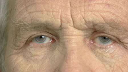 crinkle : Close up eye of an elderly man. Wrinkled face of an old man close up. An older view. Stock Footage
