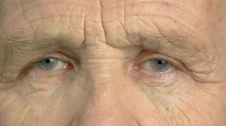 crinkle : Old man is opening his eyes close up. Wrinkled face of elderly man close up. Older man closed eyes close up.
