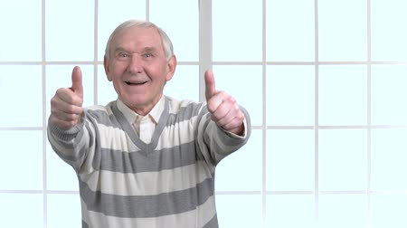 happiness symbol : Cheerful senior showing two thumbs up. Excited happy old man gesturing thumb up with two hands, office window background. Stock Footage
